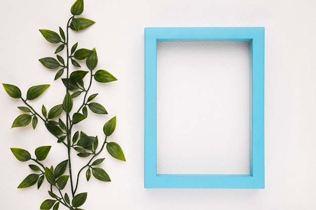 Empty blue wooden frame near the artificial plant on white background