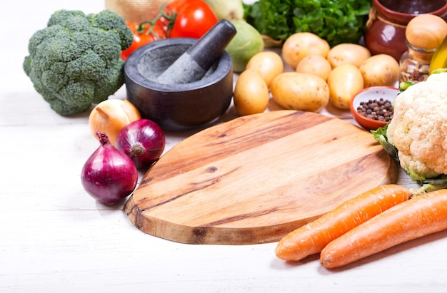 Empty board with various products for cooking on wooden table