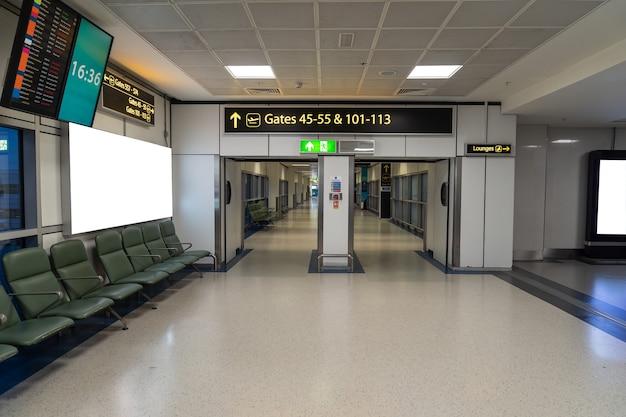 Пустые выходы на посадку со стульями, в аэропорту нет людей