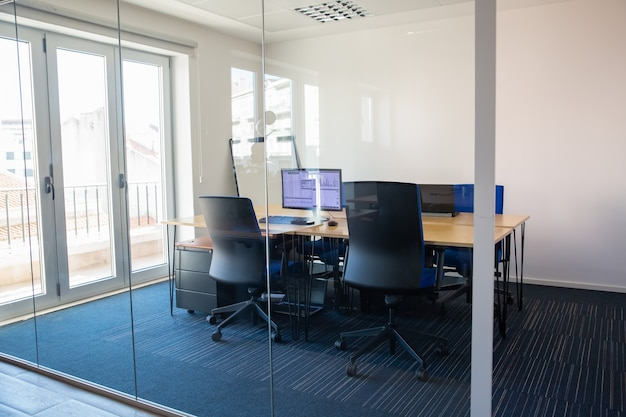유리 벽 뒤에 빈 회의실입니다. 회의 테이블, 팀 및 작업 공간을위한 공용 책상이있는 회의실. 모니터에서 거래 그래프. 사무실 인테리어 또는 상업용 부동산 개념