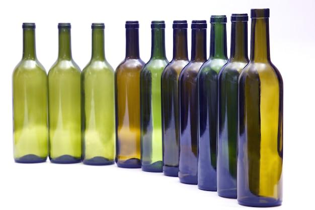 白い背景の上に一列に立っている空のボトル
