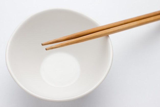 Empty bowl and chopstick isolated on white