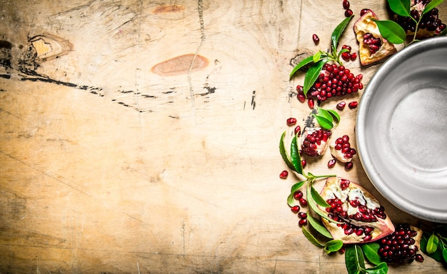 Empty the bowl of pomegranate seeds and leaves around. on a wooden table. free space for text . top view