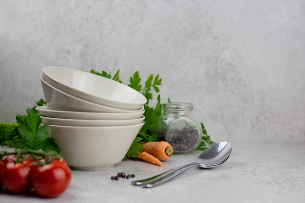 Empty bowl and vegetables with spices on a light gray concrete background.