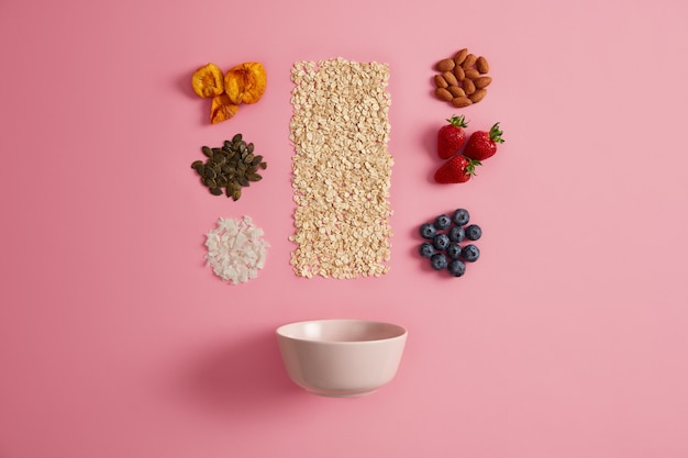 Пустая миска с овсянкой, курагой, тыквенными семечками, кокосом, миндалем, клубникой и черникой, чтобы приготовить питательный органический завтрак. концепция диеты и правильного питания. ингредиенты для еды