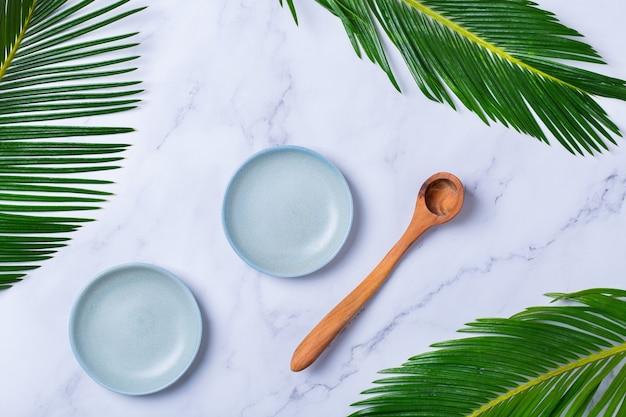 녹색 야자수 잎이 있는 세련된 대리석 배경에 빈 그릇과 계량 스푼. 자연의 아름다움과 건강 보조 식품, 웰빙 스킨케어 노화 방지 개념. 평면도, 평면도, 복사 공간