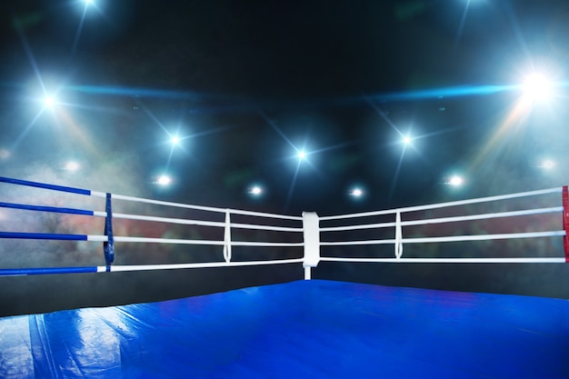 Empty boxing ring, blue flooring, view on corner with white ropes. professional arena for sport competitions and fighting tournaments, nobody