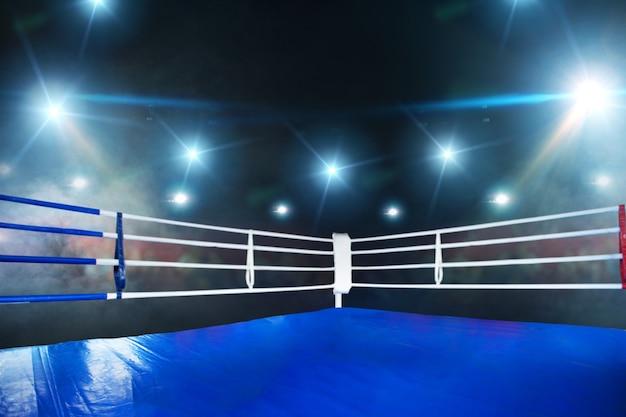 空のボクシングのリング、青い床、白いロープで角を見る。スポーツ大会やファイティングトーナメントのためのプロのアリーナ、誰も