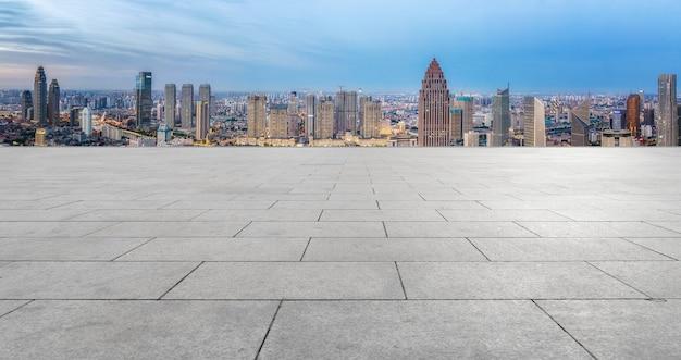 街のスカイラインの背景と空のレンガの床