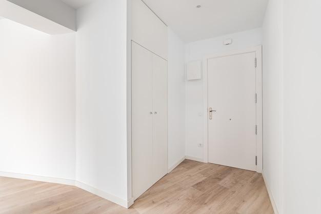 Пустой светлый вход в квартиру с закрытой дверью прихожей и гардеробной