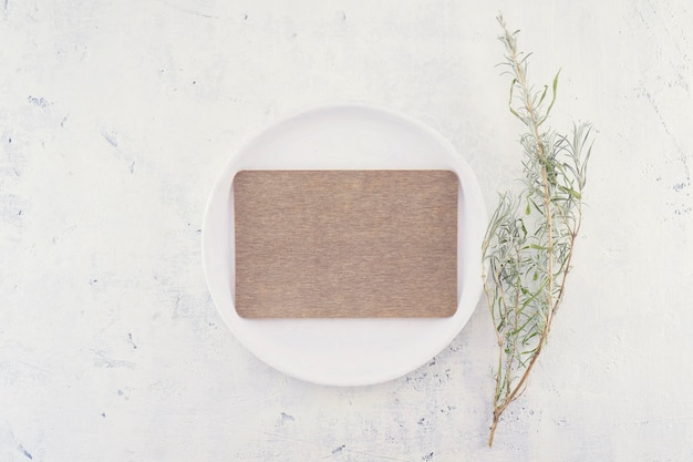 Empty brown blank business or wedding card mockup on white vintage plate
