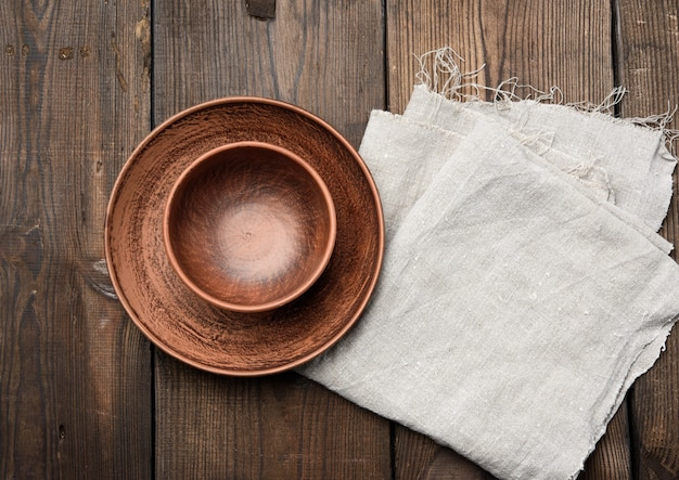 Empty brown ceramic plates on a wooden table