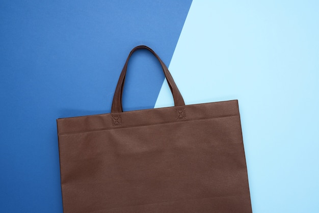 Empty brown eco bag on blue background