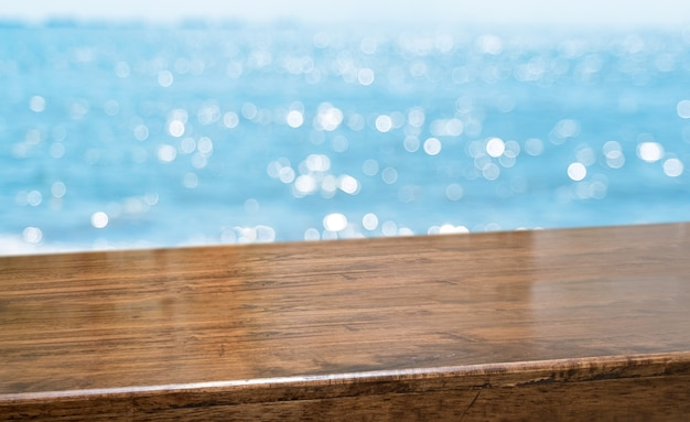 Empty brown glossy wood table top with blur sky and sea boekh background