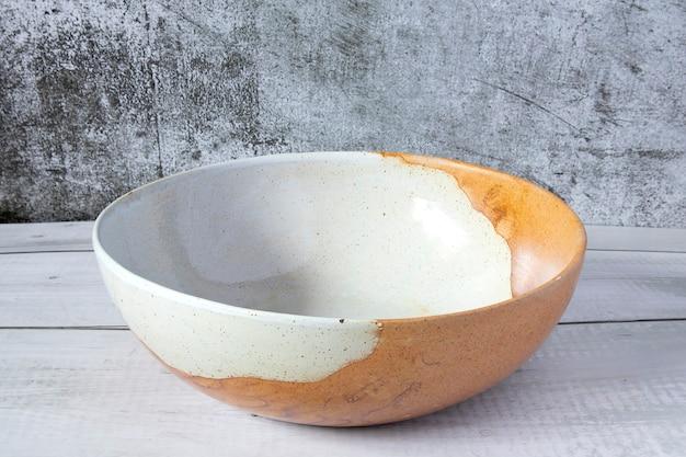 나무 탁자 위에 일본식 빈 갈색 수제 세라믹 그릇과 짙은 회색 시멘트 배경, 측면 전망.