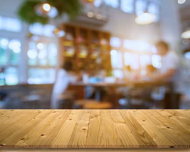 Empty brown old plank wooden board as mock up display shelf or table with blurred group of customer in coffee shop or bistro and soft bokeh from electric lamp and window lighting
