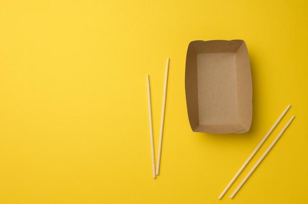 空の茶色の紙皿と黄色の背景、上面図に木製の箸。使い捨て食器、廃棄物ゼロ