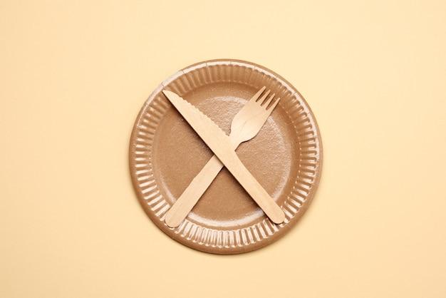 空の茶色の紙皿と木製のナイフとフォーク