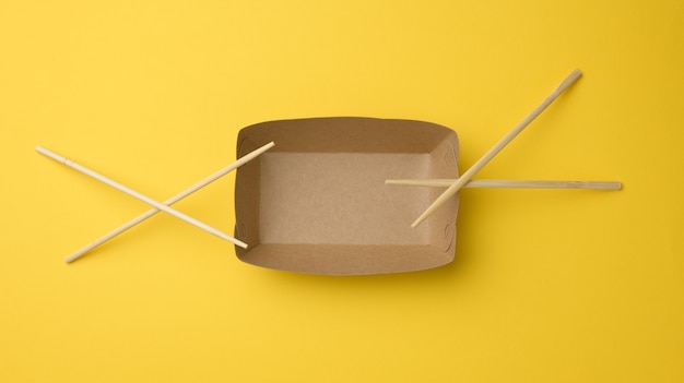 Empty brown paper plate and wooden chopsticks on a yellow background, top view. disposable tableware, zero waste