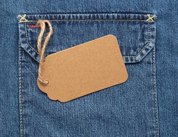 Пустая коричневая бумажная бирка на веревке, привязанной к карману джинсов