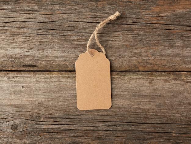 白いひもで結んで空の茶色の紙タグ。値札・ギフトタグ