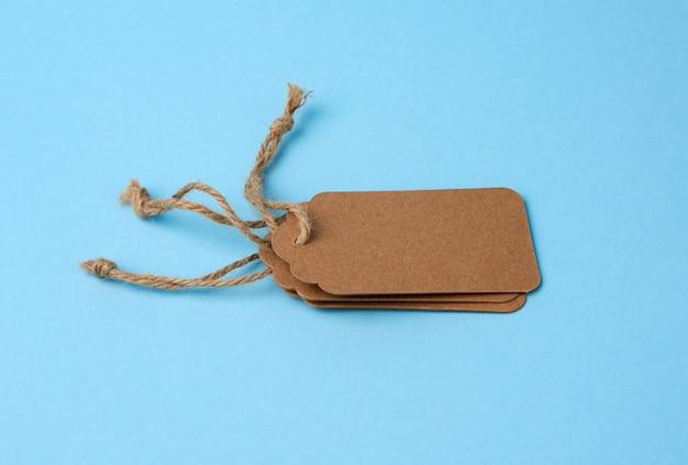 Пустые коричневые бумажные теги связаны с белой строкой. ценник, подарочная бирка, бирка продажи
