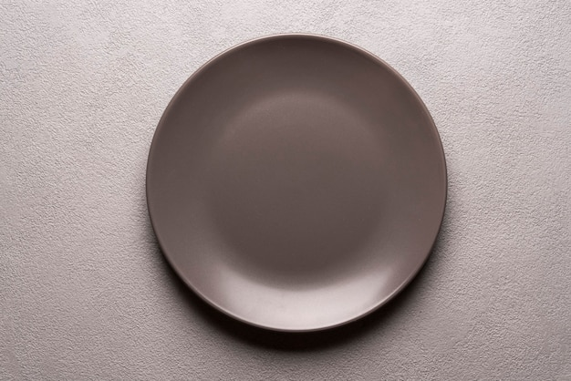 An empty brown plate on a gray table. minimalistic falt lay, mockop copyspace