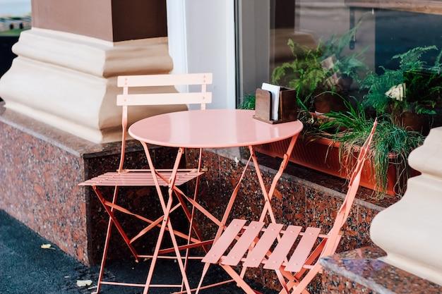 カフェの近くの通りにある空の茶色のテーブルと椅子。都会的な装飾。