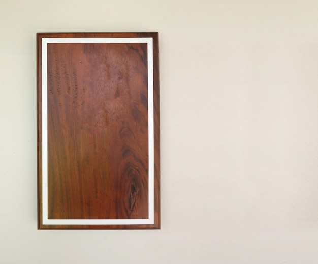 Empty brown wood frame on gray cement wall.