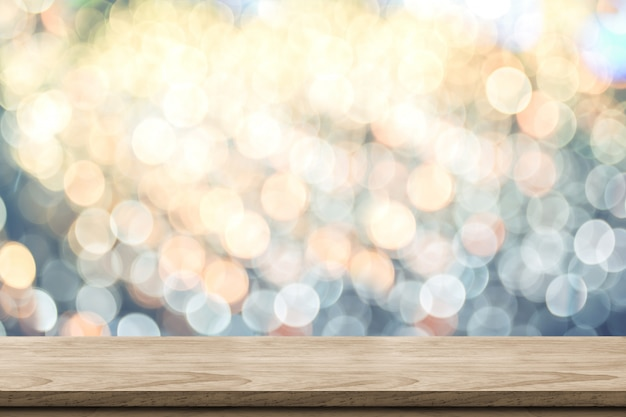 Empty brown wood table top with blur sparkling soft pastel blue and orange bokeh abstract background