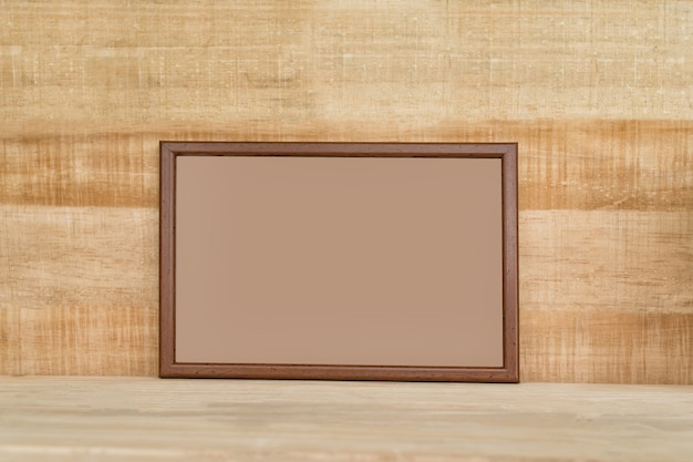 Empty brown wooden photo frame on light brown wooden wall.