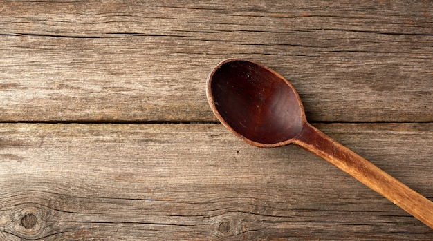 Empty brown wooden spoon on a gray wooden surface from old boards