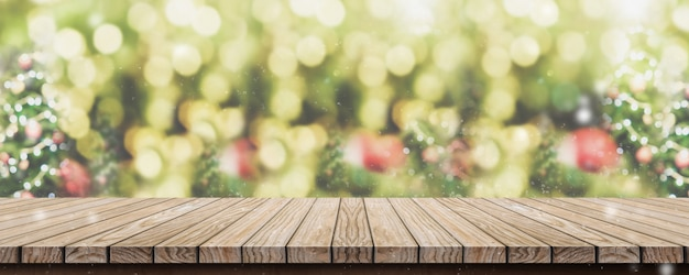 Empty brown wooden table top with abstract green blurred christmas tree