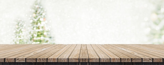 Empty brown wooden table top with abstract muted blur christmas tree and snow fall with bo