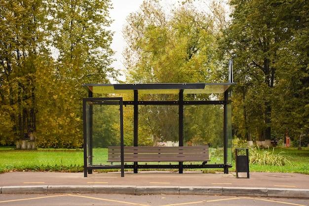 秋の空のバス停木々を背景にベンチのあるガラス張りのバス停