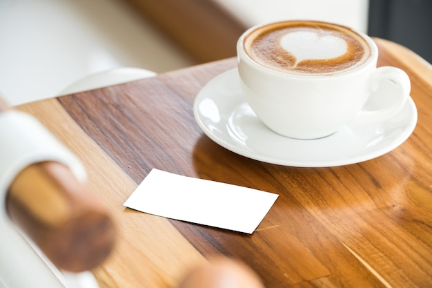 Empty business card mock up with hot coffee on wood table