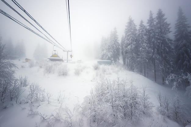 Empty cable cars are located above the forest growing on snowy hills against the backdrop of mountains and fog on a cloudy winter day. concept of trekking and skiing in winter