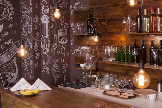 뒤쪽에 예술적인 그림이 있는 빈 카페 바 인테리어 디자인. 와인 병 . 천장에 매달린 전구.