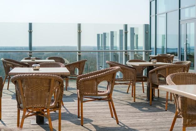 등나무 고리 버들 세공 안락 의자와 야외 테라스에 테이블이있는 빈 카페.