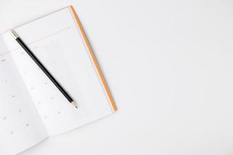 空のカレンダーブックと白い背景と分離、トップビュー、コピースペースに鉛筆