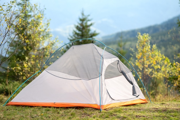 Empty camping tent standing on campsite with view of majestic high mountain peaks in distance. hiking in wild nature and active trail travelling concept.
