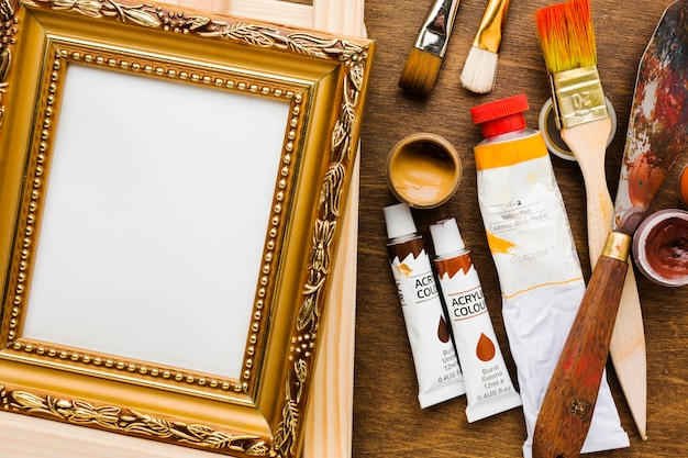 Empty canvas in golden frame and paint brushes