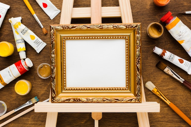 Empty canvas in golden frame and paint flat lay