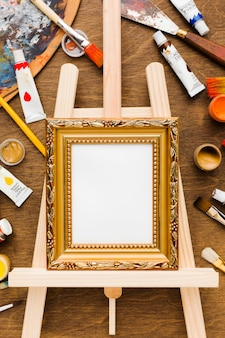 Empty canvas in golden frame and paint top view