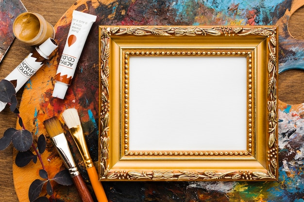 Empty canvas in golden frame and paint