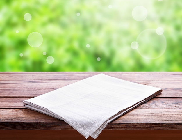 Empty canvas napkin, white tablecloth on wooden table perspective. summer landscape.