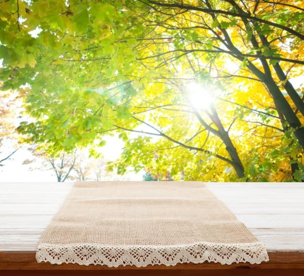 Пустая салфетка холста с кружевом, скатерть на перспективе деревянного стола. летний пейзаж.