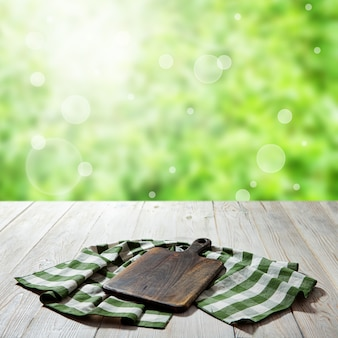 Empty canvas napkin with lace, tablecloth on wooden table perspective. summer landscape.