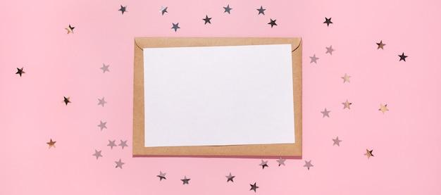 Пустая карта и звезды конфетти льются на пастельный розовый фон, вид сверху. плоская планировка. концепция праздника, приветствия или хороших новостей. шаблон макета. вид сверху. пустой флаер