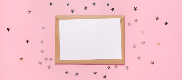 Empty card and confetti stars pours on a pastel pink background, top view. flat lay. holiday, greeting or good news concept. mockup template. top view. blank flyer